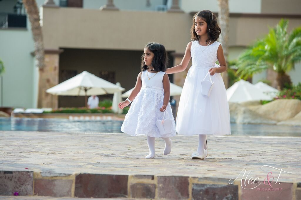 two girls that are flower girls dressed in white.