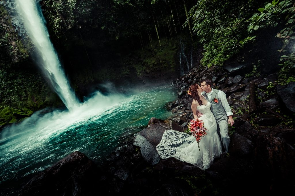 couple kissing in front of water fall in central america