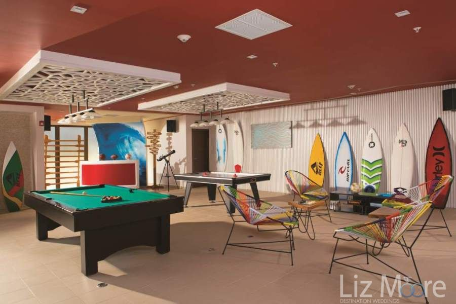 Open games area with pool table shuffleboard and surfboards