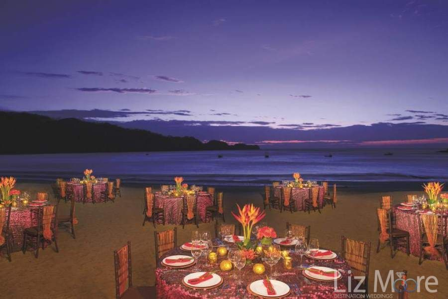 Wedding reception set up on the beach beside the ocean with a beautiful color flowers