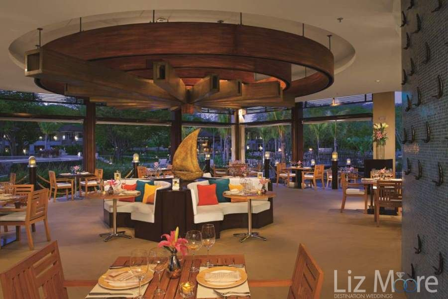 Restaurant in the evening with different colored cushions marble floors and beautiful wood ceiling structure