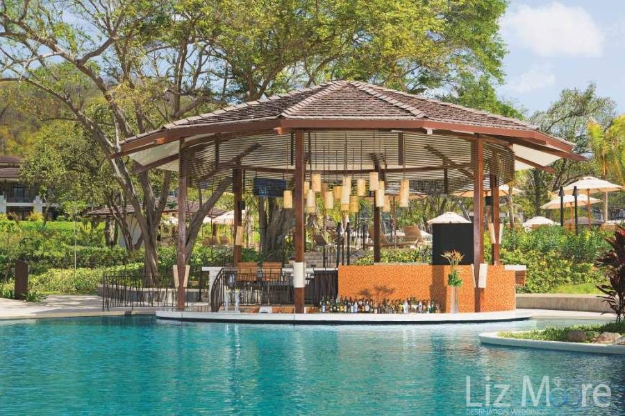 Open swim up bar with premium drinks served and seating in the pool
