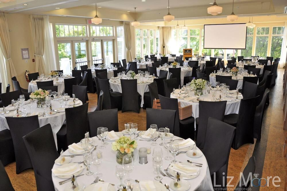 indoor ball room with a beautiful tables and flowers set up and windows overlooking the gardens