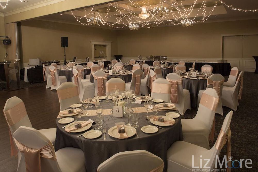 wedding ballroom set up with pink ribbons and pink table decor and white lights