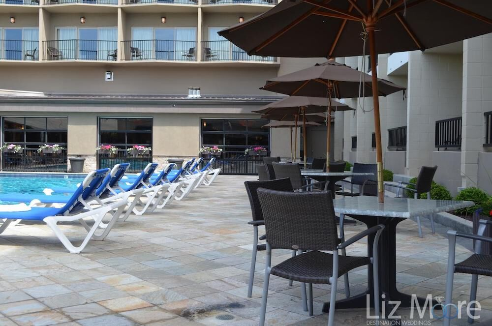 Outdoor seating chairs table and umbrella beside the lounge chairs beside the main pool
