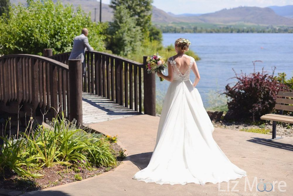 Bride beside the bridge overlooking  overlooking Lake Osoyoos with groom on the bridge