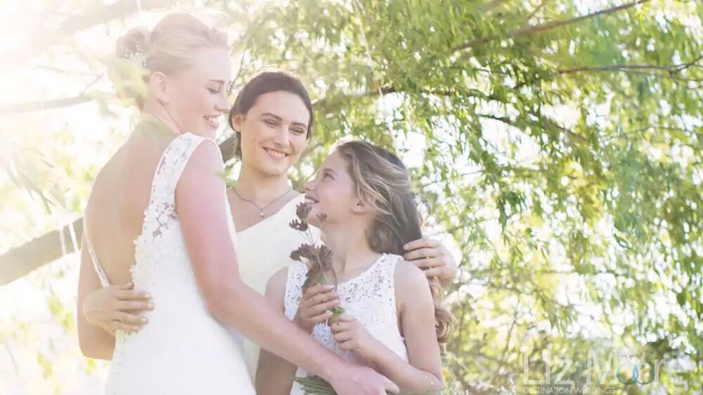Bride and flower girl head bridesmaid Sharing flowers under a tree