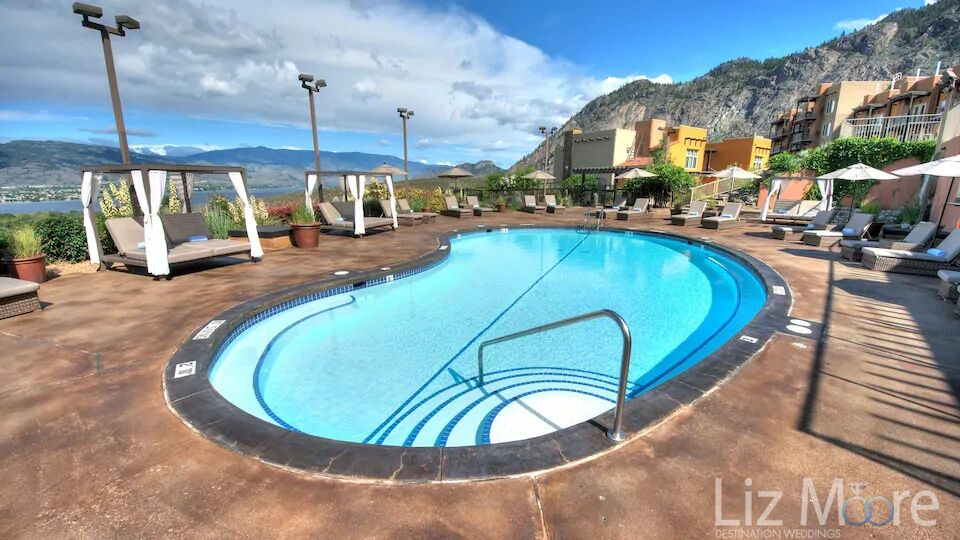 Main outdoor pool area with lounge chairs and views of the lake and mountains