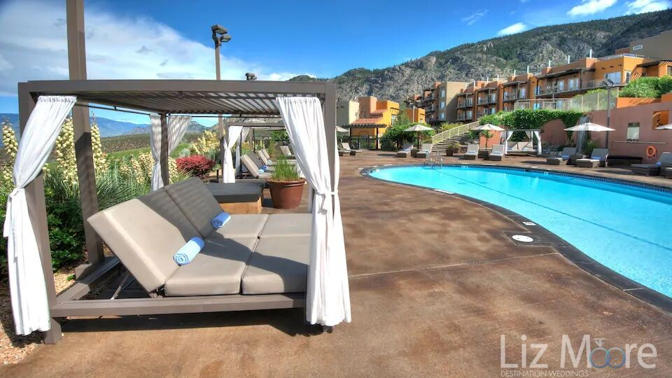 Large cabana loungers on the pool deck beside the pool with a room buildings in the background