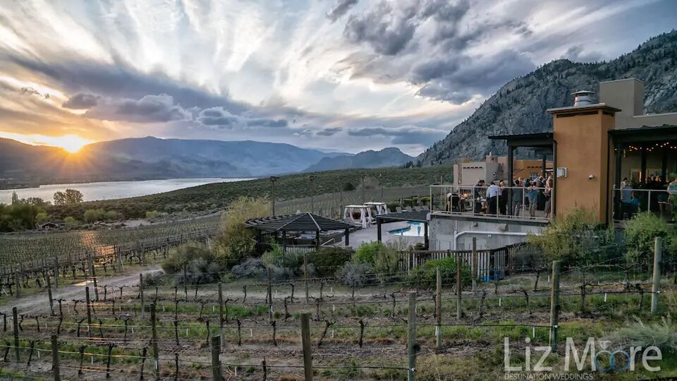 Resort in the evening at sunset with reception on the upper deck and vineyards lakes and mountains in the background