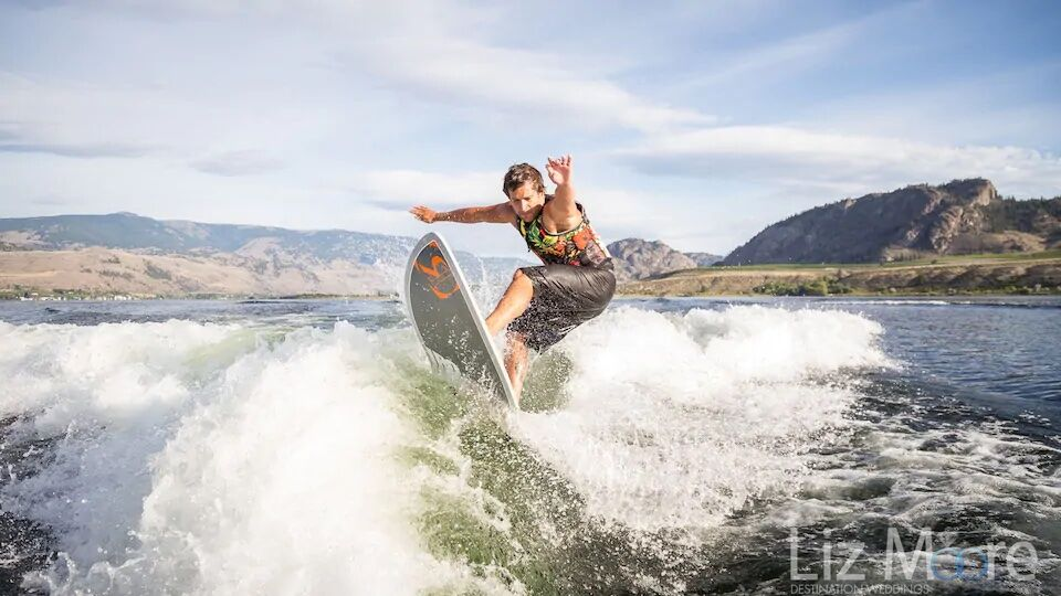 Wakeboarder on Osoyoos lake beside the property with mountains in the background