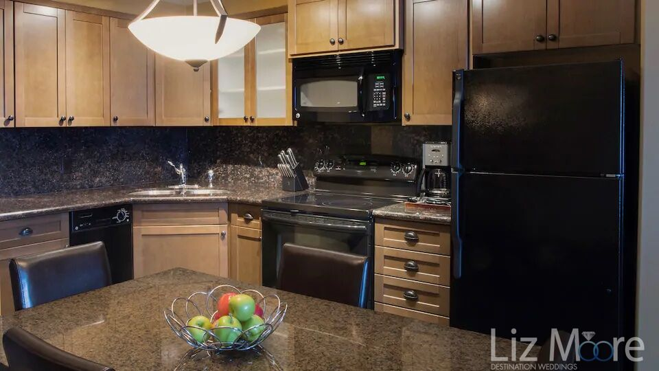 Full kitchen suite located in bedroom with fridge stove and table and chairs