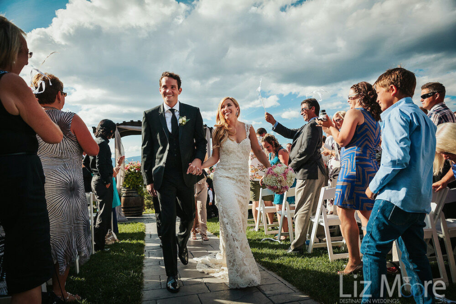 Wedding couple walking down the aisle with guests cheering Neil Slattery Photography