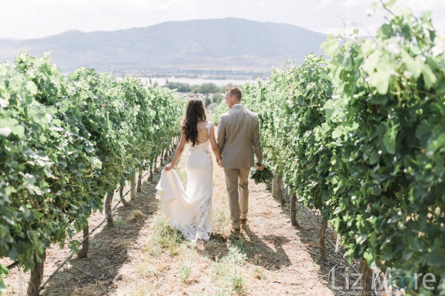 Wedding couple in Vineyard walking along the pathway with Okanogan lake in the background