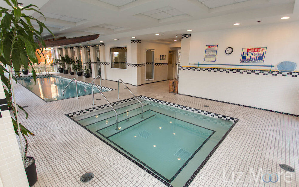 indoor pool with hot tub beside it and palm plants  on white tile flooring