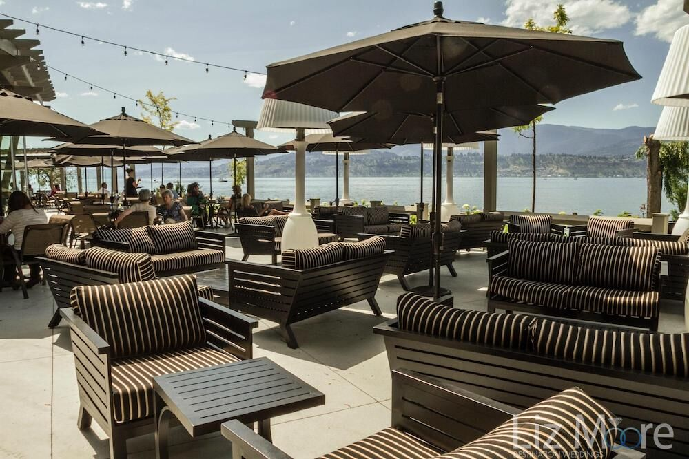 Outdoor seating chairs couches and dining Area with umbrellas overlooking the lake