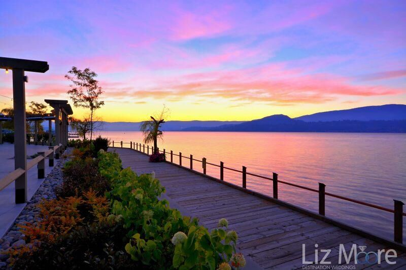 Evening deck area surrounding the property and shrubs at sunset with the mountains in the background and the lake