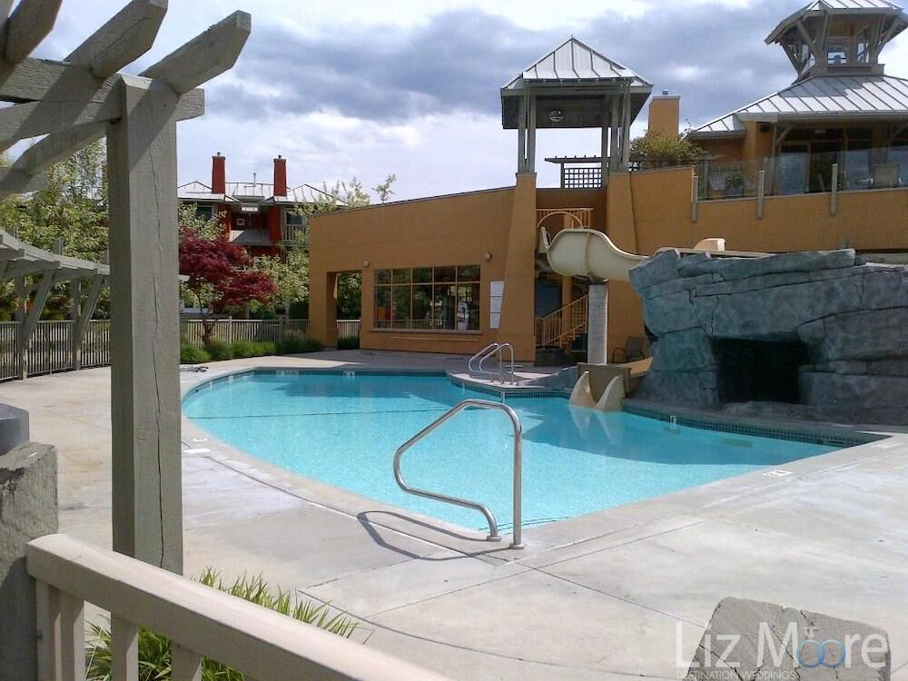 Outdoor swimming pool area with waterslide and deck area