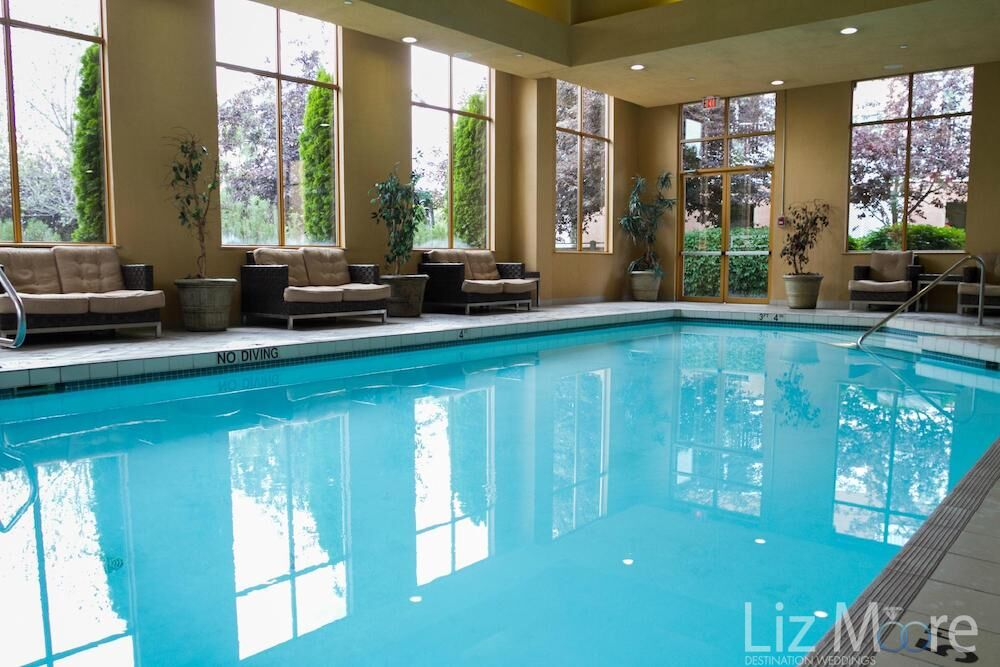Indoor pool area with lounge sitting and large glass windows overlooking the grounds