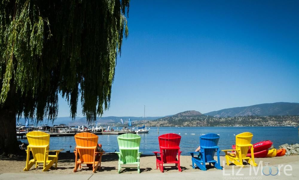 Waterfront beach chairs in different colours on the beach beside the dock and the leg
