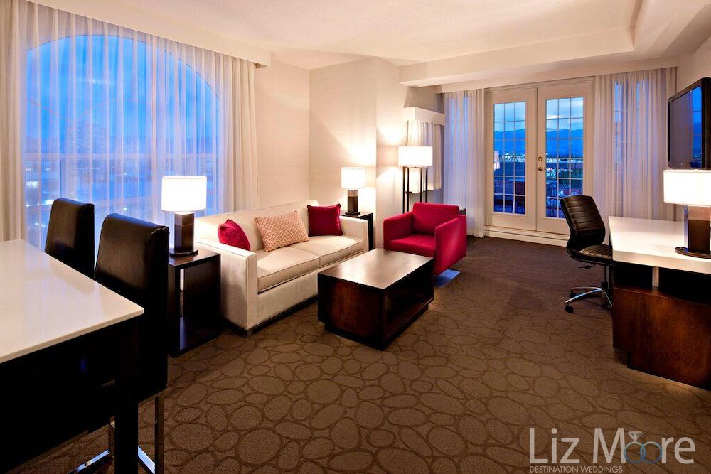 mode suite with beautiful white couch wooden table cheers red chair and view of the lake