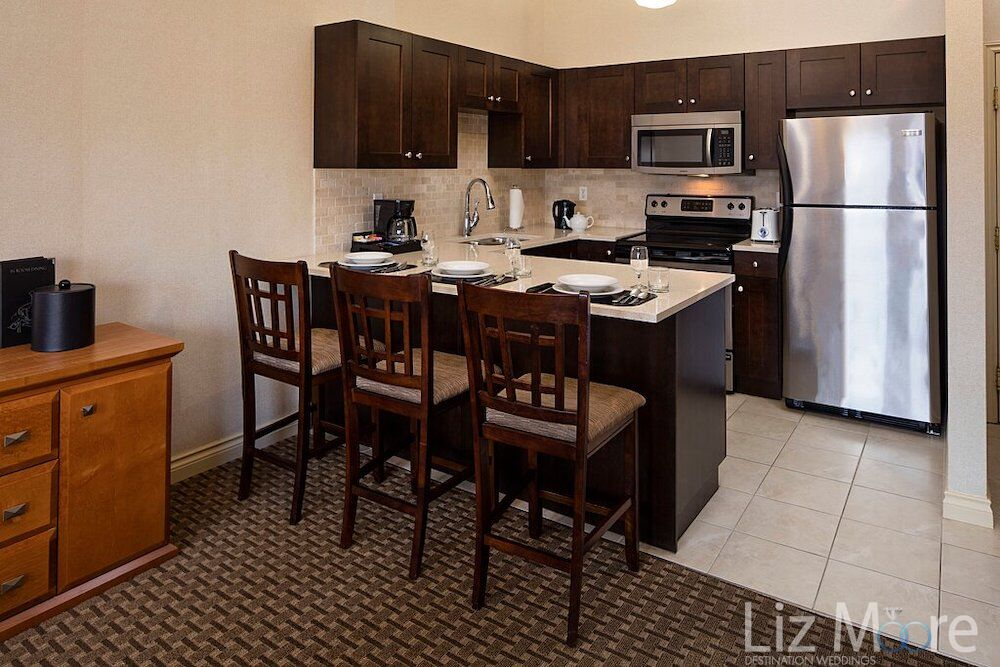 One bedroom condo kitchen with island seating fridge stove and carpet