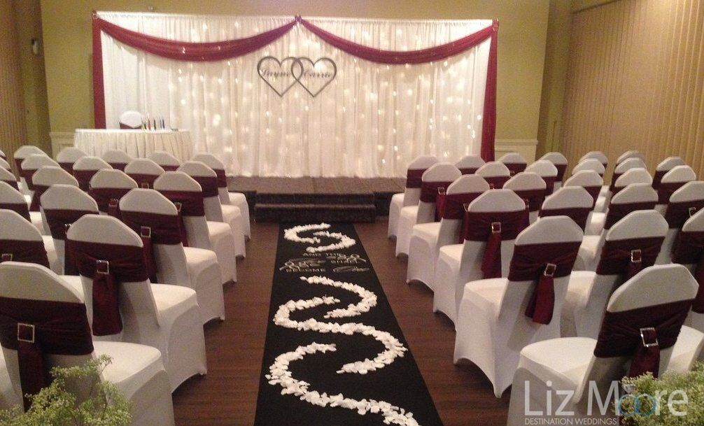 indoor wedding ceremony set up with white flower runner and red velvet chair ribbons