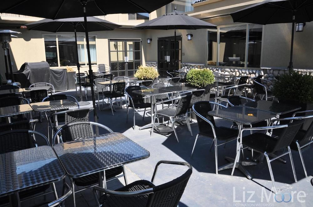 outdoor patio lunch seating area with tables chairs and umbrellas