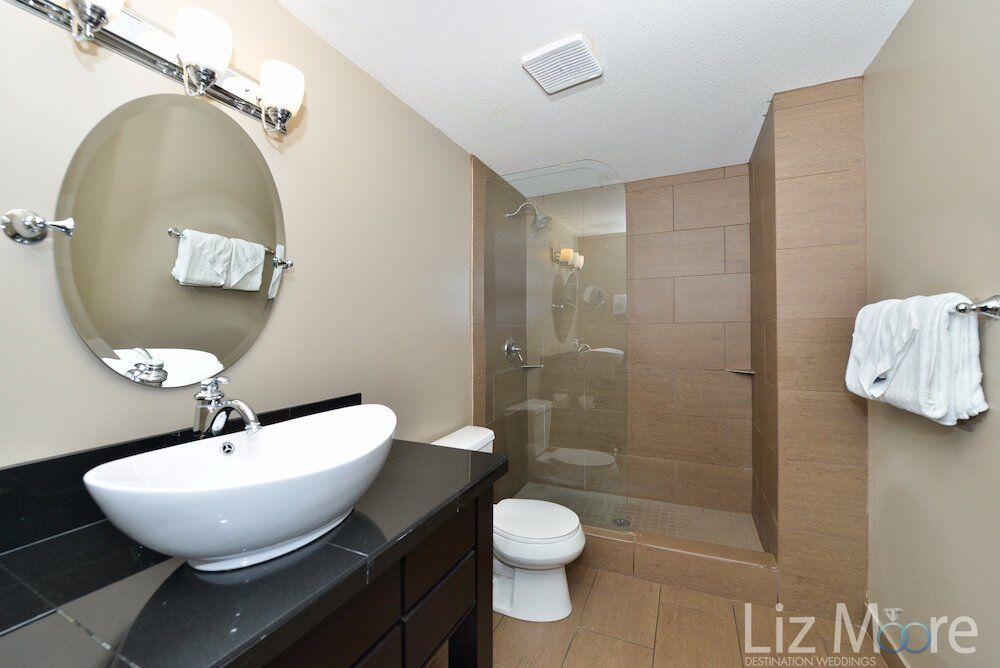 bedroom bathroom area with white vanity sink and glass shower
