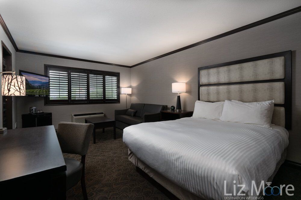 king bedroom with white duvet cover and couch and table with lamps