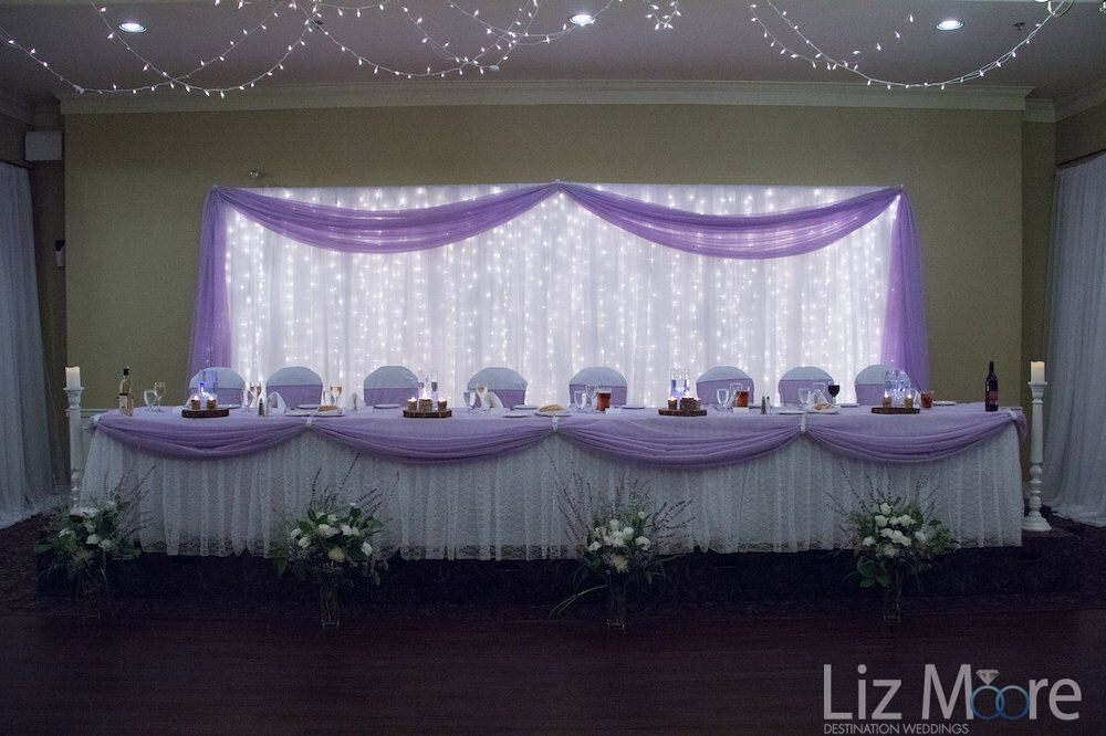 Indoor ballroom wedding reception set up with soft ceiling lighting and lilac wedding decorations
