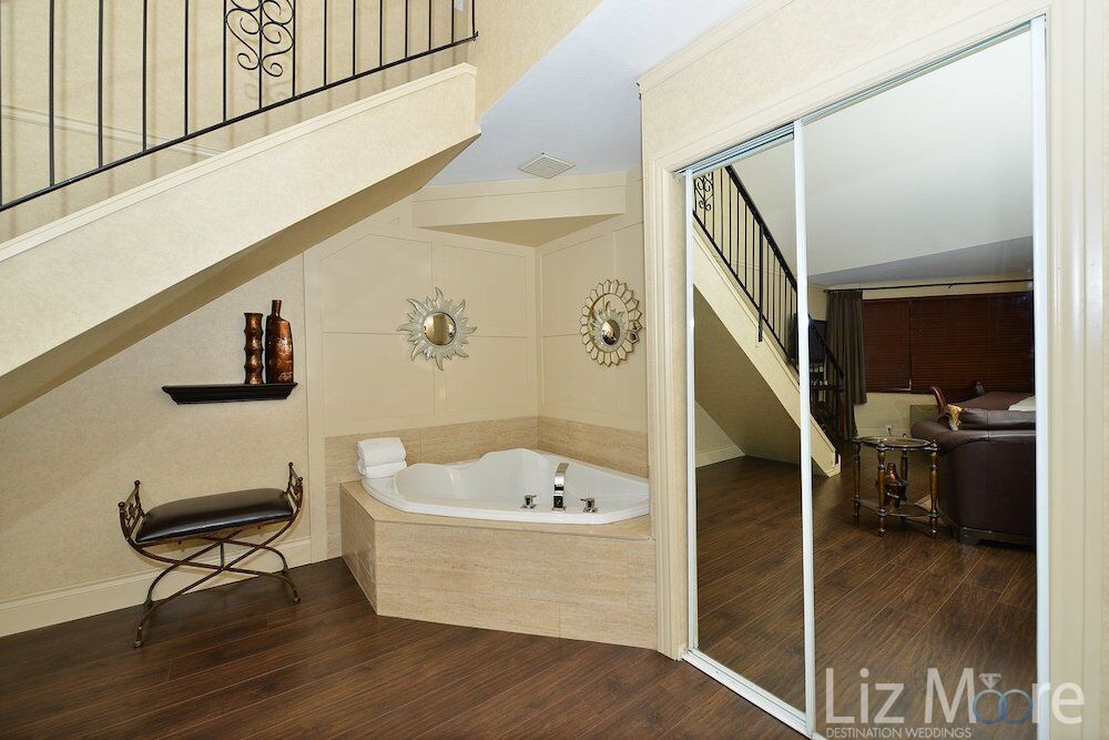 bedroom suite with soaker tub, closet and stairway to upstairs bedroom.