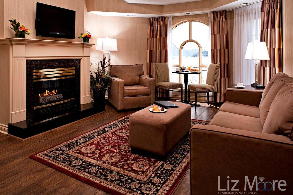 Two bedroom suite living area with a beautiful brown Velore coaches, chair View of the lake and fireplace