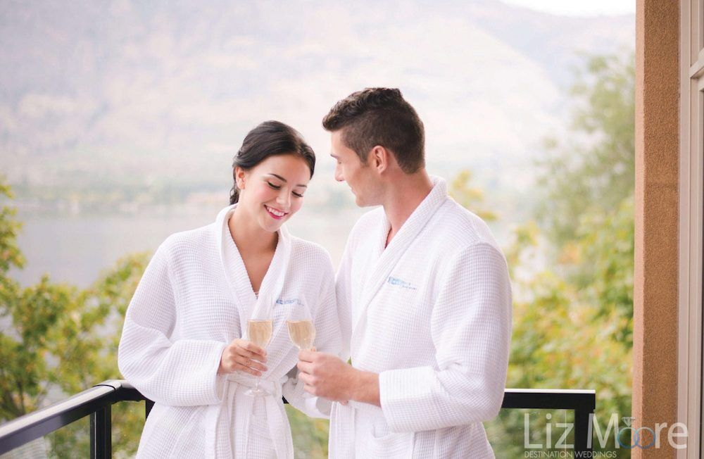 honeymoon couple standing on the balcony with Hotel robes enjoying a glass of white wine
