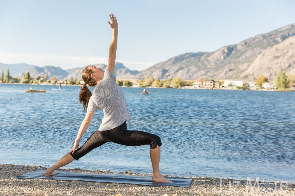 resort guest doing yoga on a yoga mat by Lake Osoyoos