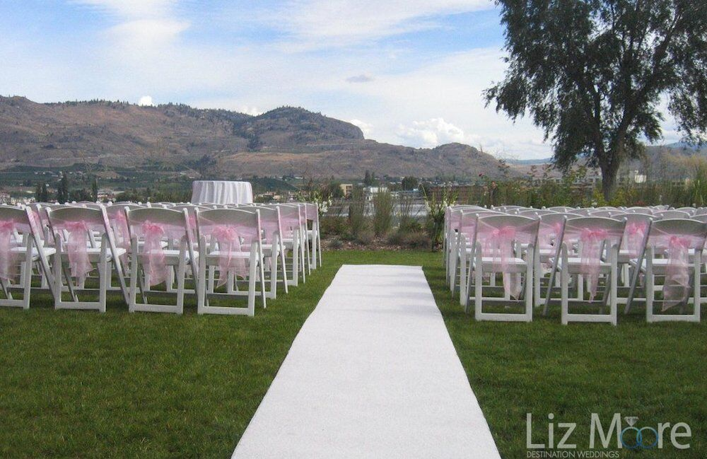 chairs set up with pink ribbons and white runner for wedding ceremony site