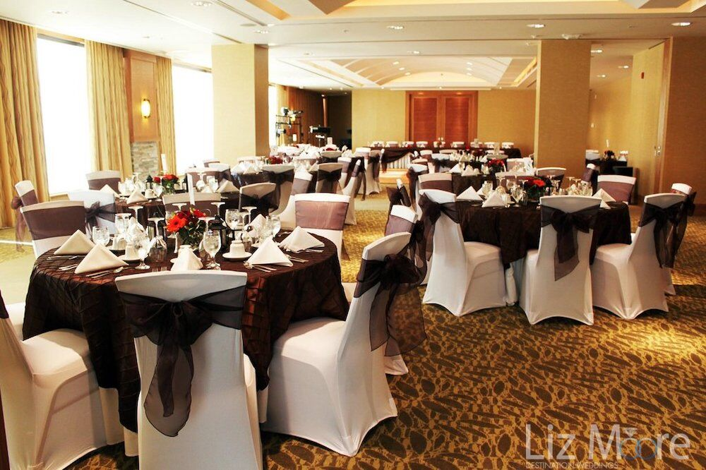indoor a ballroom wedding reception set up with a tables chairs and Brown ribbons