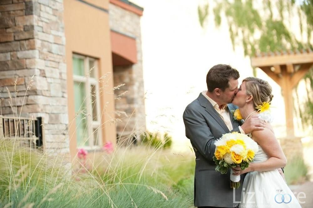 wedding couple embracing with a beautiful yellow and white Bouquet on the hotel lawn