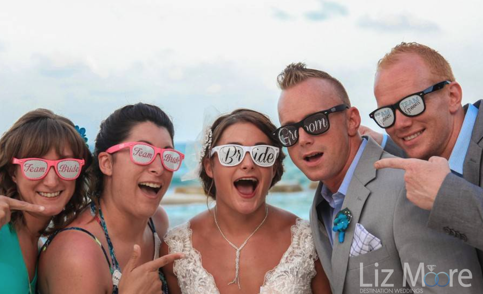 Bride grom and guests with sunglasses on beach at destination wedding