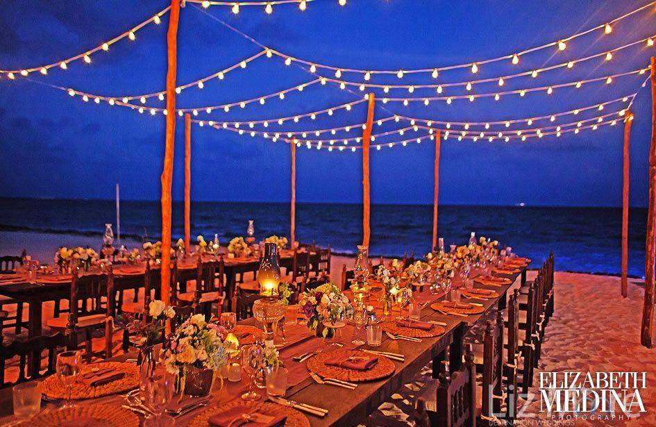 destination wedding reception on the beach with tiki lights and flower decor on tables