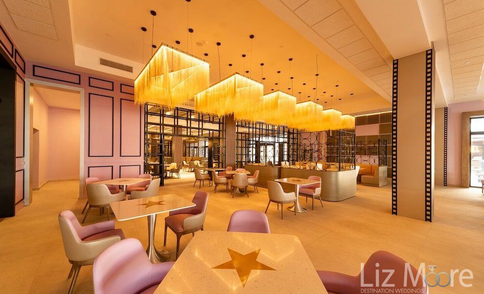 Dining room at planet hollywood beach with yellow chandeliers and pink chairs
