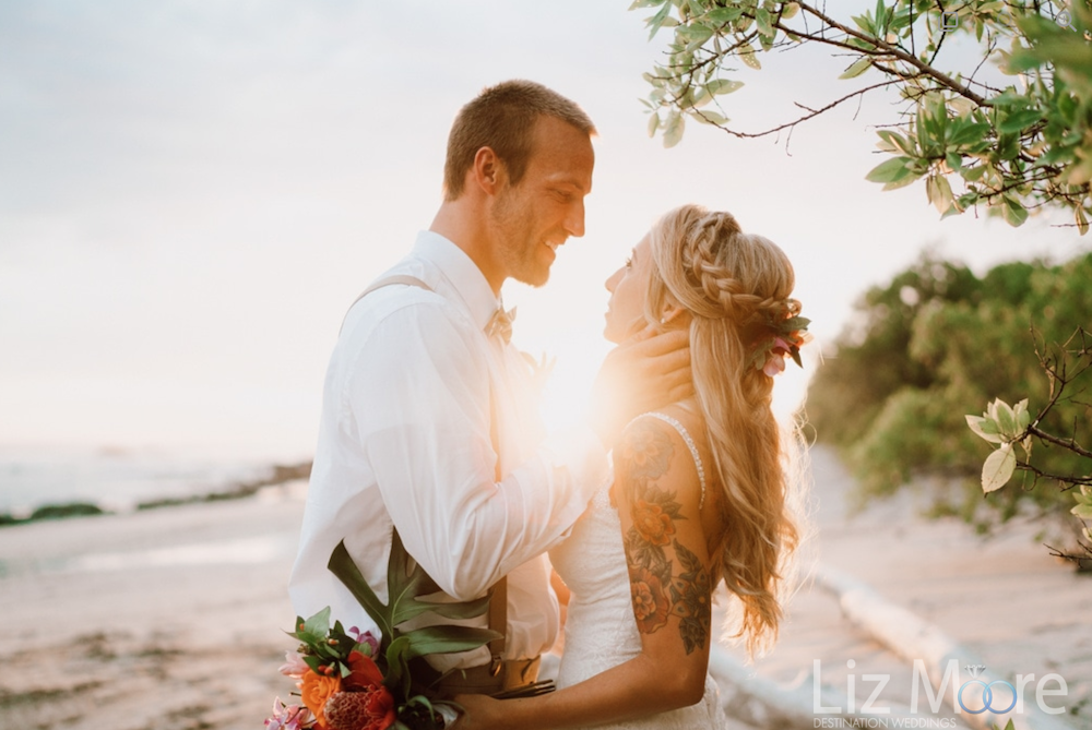 Sunset beach wedding with bride and groom and palm trees and beach